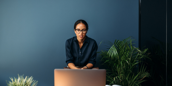 woman looking at the benefits of video conferencing on her laptop