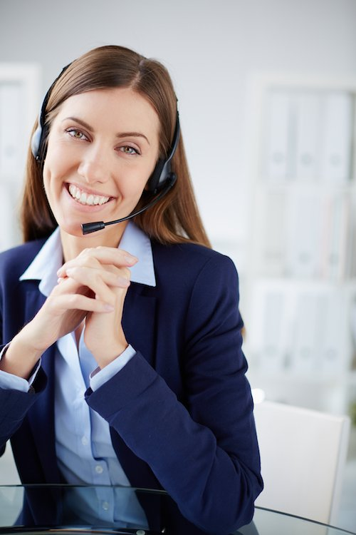 woman with business phone service headset smiling at camera